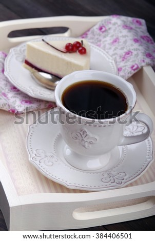 Cheesecake and coffee on white vintage wooden tray and vintage metal candlestick on a wooden background