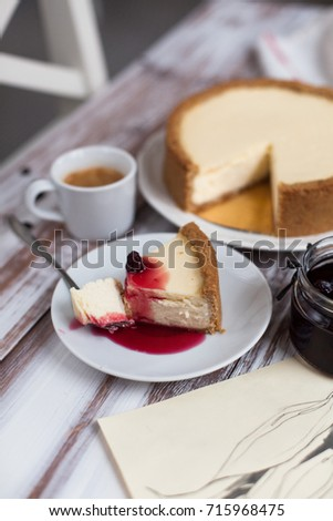 Cheesecake, coffee, jam,towel,fork and pencil drawing on the wooden table.Side view.