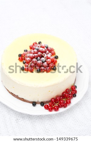 cheesecake decorated with red and black currants, vertical, top view - stock photo