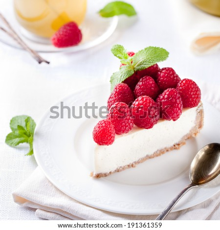 Cheesecake slice with fresh raspberries and mint leaves on a white plate. - stock photo