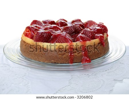 cheesecake topped with strawberries and a glaze of crushed berries