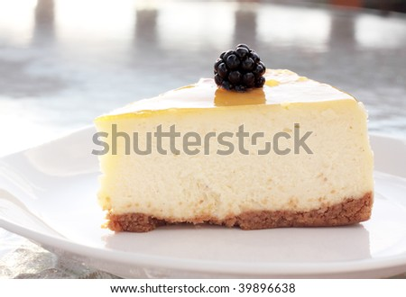 Cheesecake with a single blackberry shimmering in the afternoon sun - stock photo