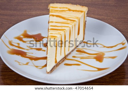 Cheesecake With Carmel Drizzled on Top Served on a White Plate - stock photo