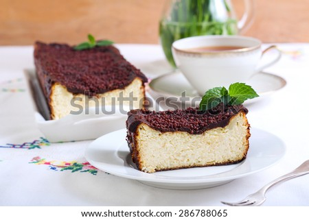 Cheesecake with chocolate topping and cup of tea