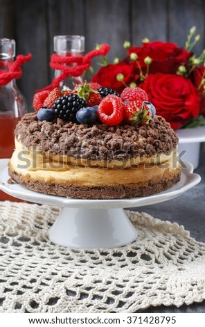 Cheesecake with chocolate topping decorated with summer fruits: raspberries, strawberries, blueberries and blackberries. - stock photo