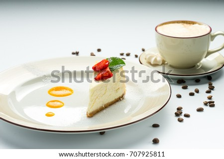 Cheesecake with strawberries, mint and orange marmalade on the plate