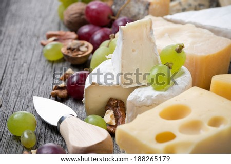 cheeses, grapes and walnuts on a wooden background, close-up