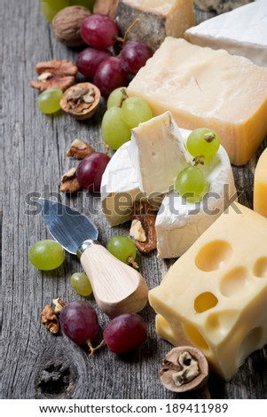 cheeses, grapes and walnuts on a wooden background, top view, vertical