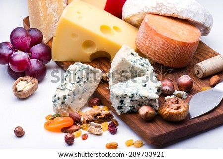 Cheeses with dried fruits and nuts on wooden board  - stock photo