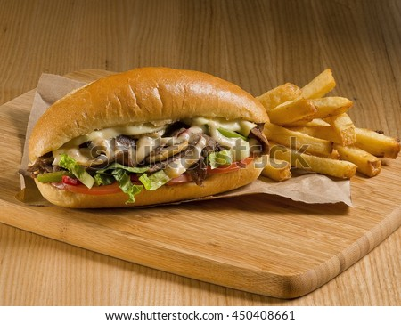 cheesesteak sandwich on cutting board with fries - stock photo