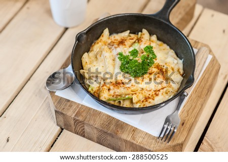 Cheesy baked macaroni and cheese pasta portion with parmesan sprinkled on top - soft focus point - stock photo