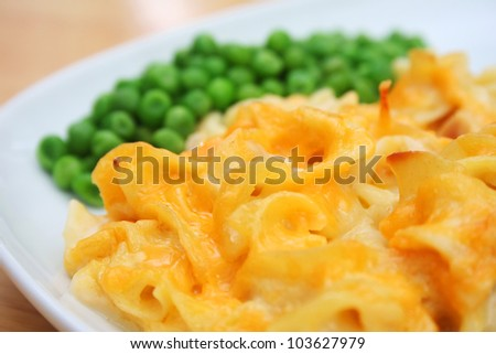 Cheesy Noodle Casserole and Peas on a White Dish - stock photo