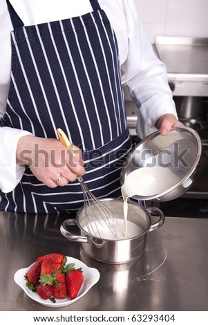 Chef add milk in a pan - stock photo