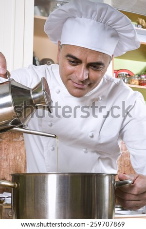 Chef adding oil to a stew.