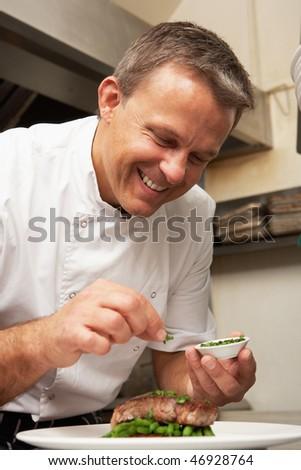 Chef Adding Seasoning To Dish In Restaurant Kitchen - stock photo