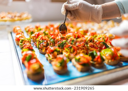 Chef adding special dressing on colored canapes - stock photo