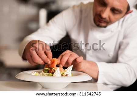 Chef adding topping for smoked salmon salad - stock photo