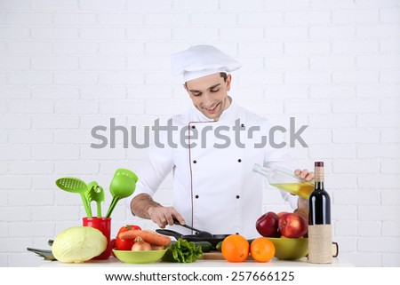 Chef at table with different products and utensil in kitchen on white wall background