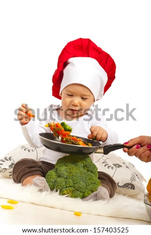 Chef baby taking macaroni from frying pan  - stock photo
