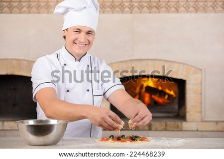 Chef baker in white uniform is making pizza at the kitchen. - stock photo