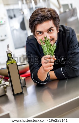 Chef checking the freshness of a bunch of fresh herbs by smelling the aroma before using them in his cooking to season and flavor the food - stock photo