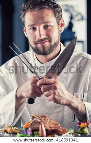 Chef. Chef funny. Chef with knife and fork arms crossed. Professional chef in a restaurant or hotel prepares or cut up T-bone steak. Chef preparing steak. Cook for their work on catering - stock photo