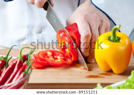 Chef chopping a red bell pepper, studio shot