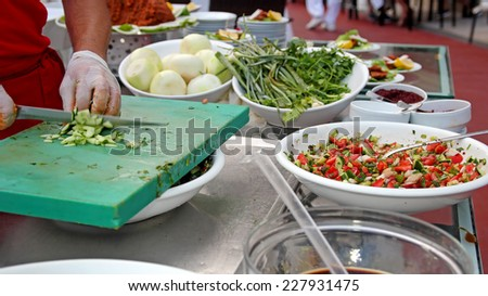 Chef Chopping Salad Ingredients. Making salad buffet.  Chef Chopping Vegetables. Chef Making Salad in a restaurant. - stock photo