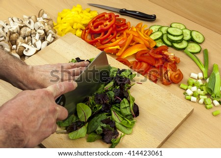 Chef chopping some babyleaf salad leafs with a cleaver knife on a wooden chopping board aside some mixed vegetables - stock photo