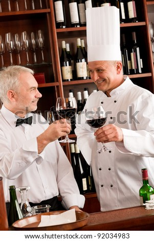 Chef cook and waiter toasting with wine smiling in restaurant - stock photo