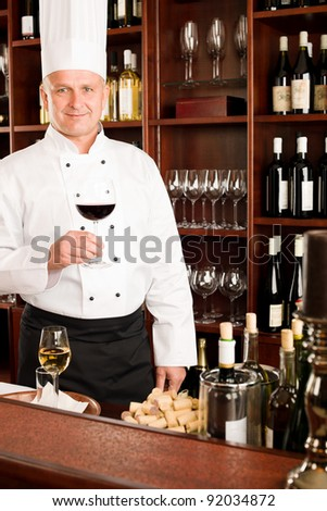 Chef cook hold glass of red wine in restaurant bar - stock photo