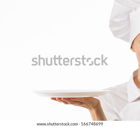 Chef cook holding an empty plate on white background - stock photo