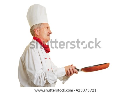 Chef cook holding frying pan with both hands while cooking