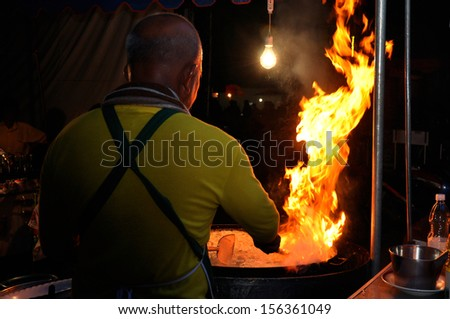 Chef cook making a show with flames while cooking in a night market. - stock photo
