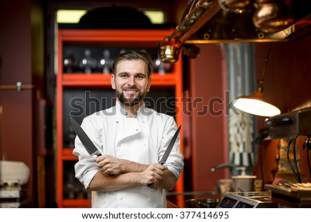 Chef cook portrait with knifes at the luxury red restaurant kitchen interior - stock photo