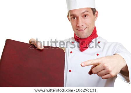 Chef cook recommending menu card with his index finger - stock photo