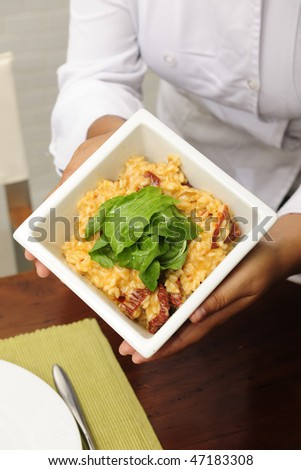 Chef cook showing a plate with her tasty  risotto, close-up - stock photo
