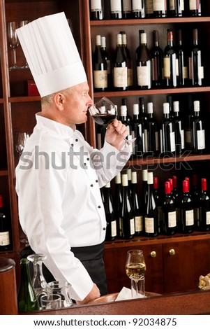 Chef cook smell glass of red wine in restaurant bar - stock photo