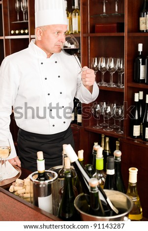 Chef cook taste glass of red wine in restaurant bar