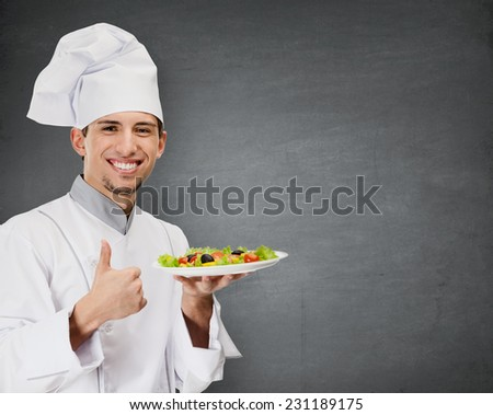 Chef cook with vegetable salad dish thumbs up, grey background - stock photo