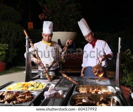 chef cooking at berbecue dinner buffet - stock photo