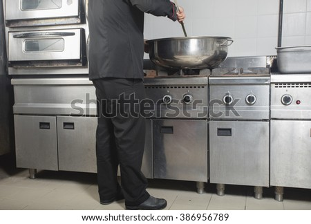 chef cooking at commercial kitchen - stock photo