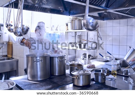 Chef cooking at commercial kitchen - hot job! - stock photo