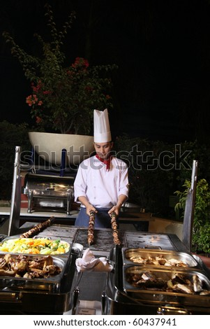 chef cooking at dinner buffet barbecue at hotel - stock photo
