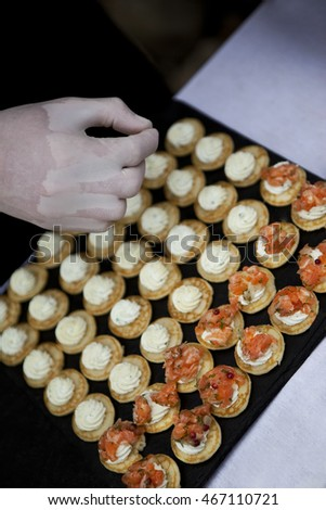 Chef cooking blini with smoked salmon and herbs cream