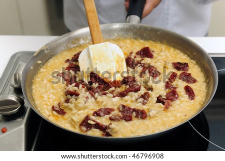 Chef cooking risotto with dried tomato stirring - stock photo