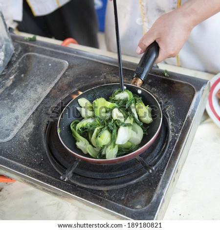 Chef cooking vegetables on stove, Mingsha Shan, Dunhuang, Jiuquan, Gansu Province, China - stock photo