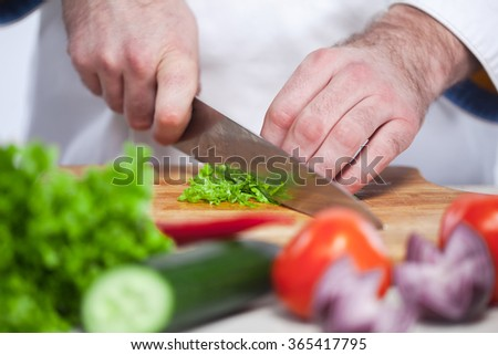 Chef cutting a green lettuce his kitchen - stock photo