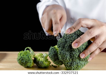chef cutting fresh green broccoli on a wooden board