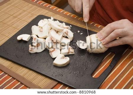 chef cutting mushroom on black board - stock photo